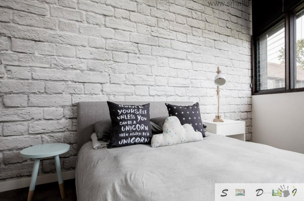 White brickwork in the white bedroom with original black cushions