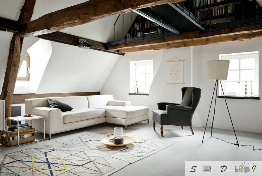 Unusual two-levelled apartment with open massive wooden beams and unique IKEA armchair as the focal point