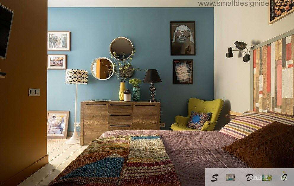 Blue wall and mirrors with paintings on it and decorated chandelabres of lamps in the bedroom