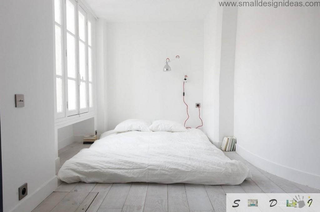 Absolutely white bedroom with mattress on the wooden floor and accent red wired lamp