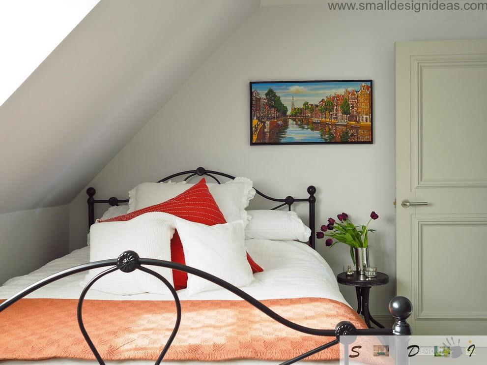 Bedroom with wrought bed and white and red linen and pillows stylistic in the Dutch apartment