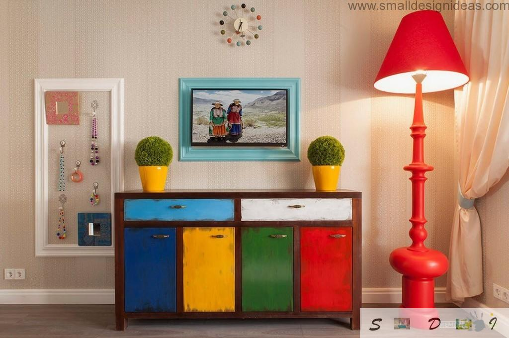 Colorful chest of drawers in the modern bedroom interior with red lamp