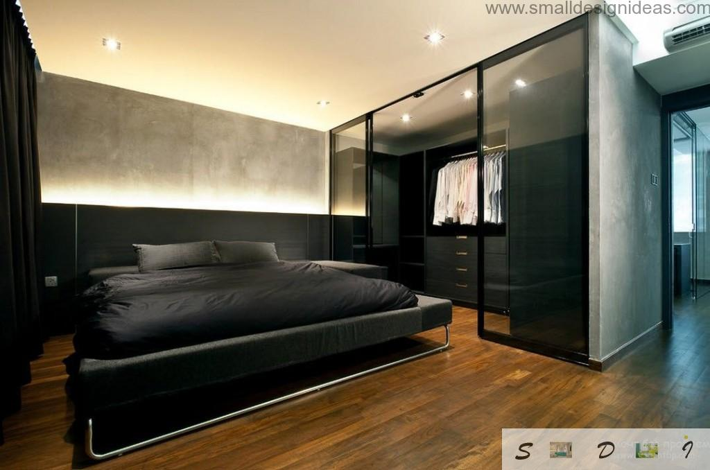 Chic black bed in the dark interior of the men`s bedroom with wardrobe full of fashionable clothes