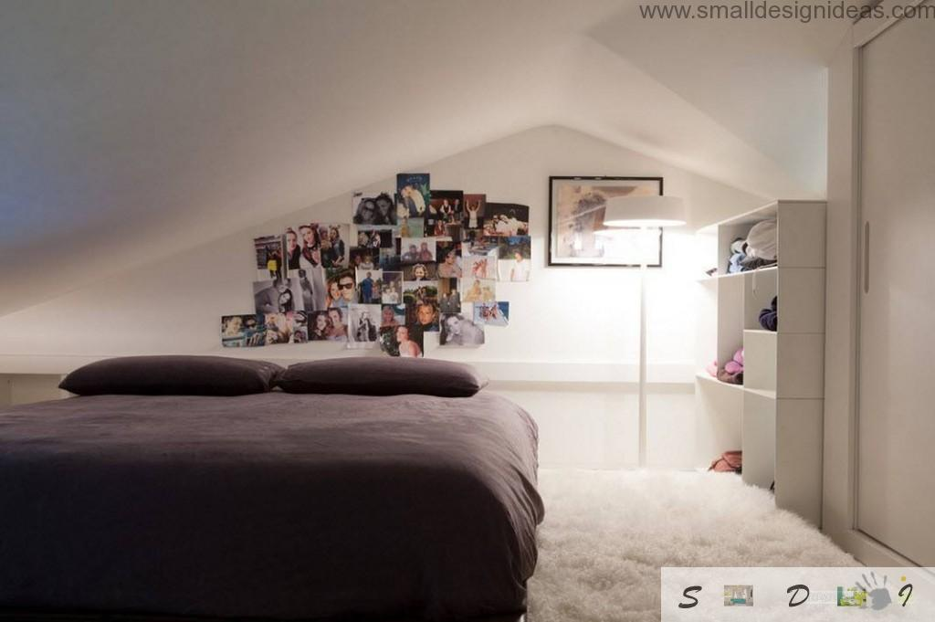 Low-key bedroom with dark bed and photocollection on the white wall