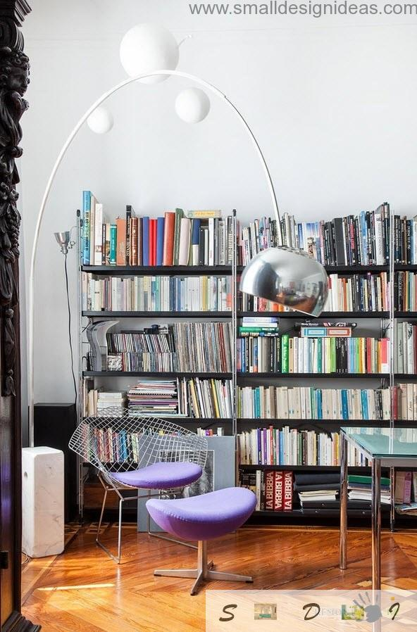 Unusual library with chrome lamp and purple chairs. Eclectic decoration
