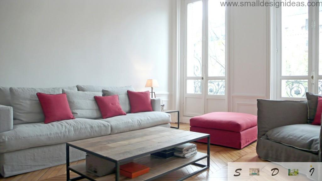 Red pillows and poufe as a contrasting spots of modern minimalistic interior of the living room with IKEA