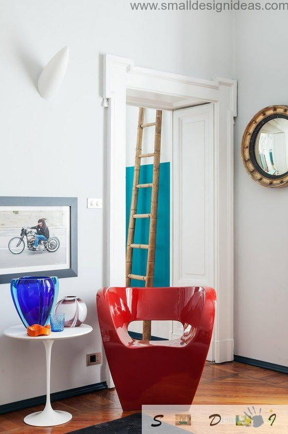 Bright red plastic armchair and wooden ladder at the hall - decorative elements of frivol;ous design of Italian apartment