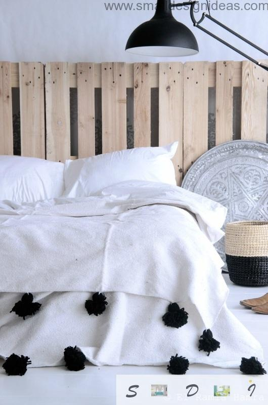 White cover on the unique pallet made bed with headboard
