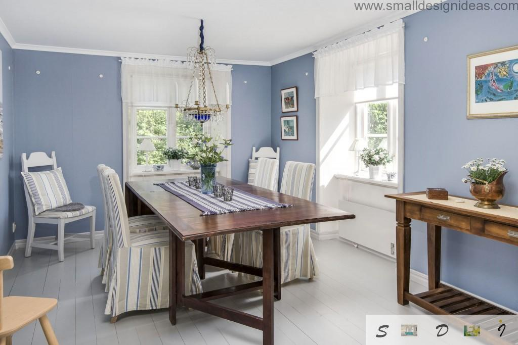 Classic dining room interior with blue walls and dark wooden furniture