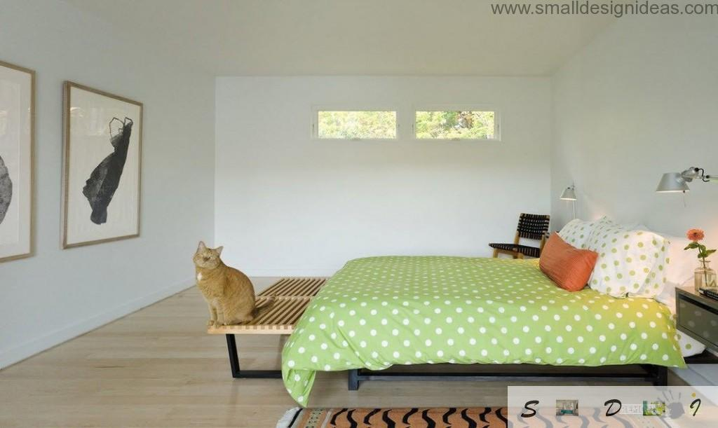 Nice Asian interior of the bedroom with green dotted coverlet over the IKEA bed and the pet in the bench near