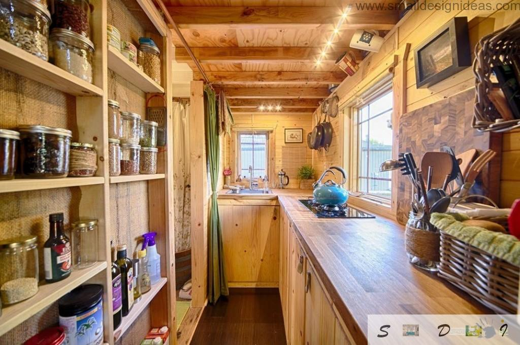 Kitchen with all necessary elements and open shelvings in the design of the wooden home on wheels
