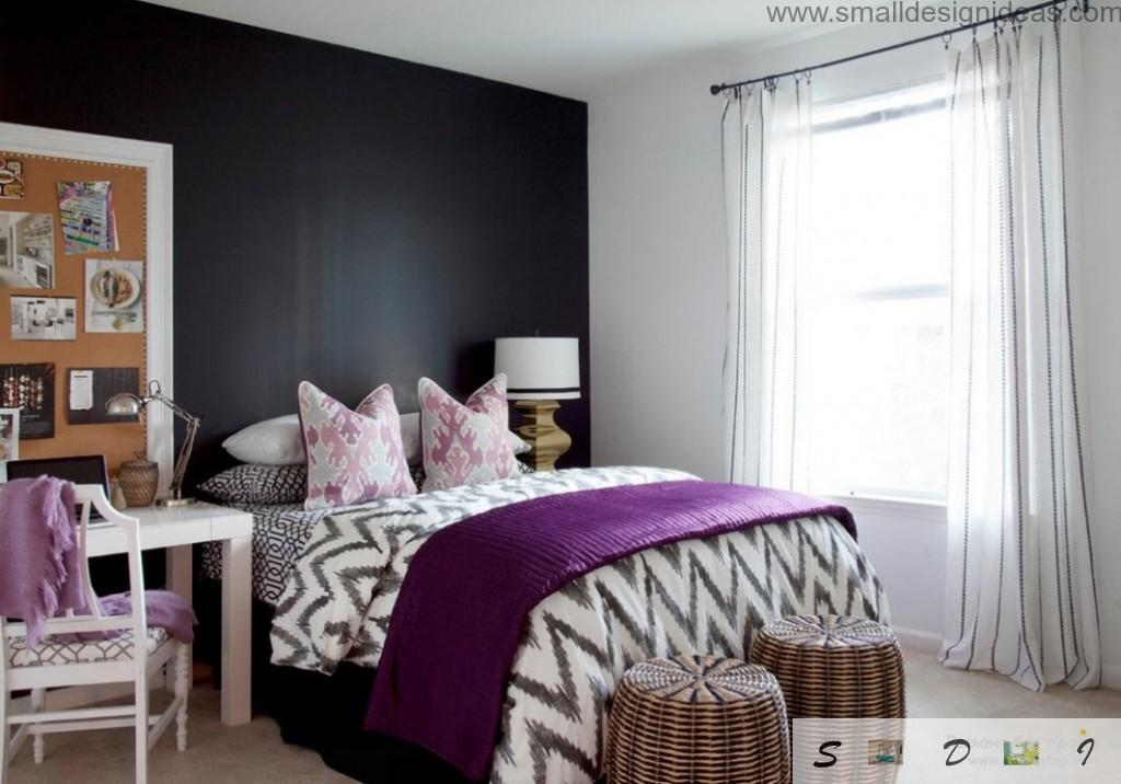 Unique bedroom design in the apartment with black contraatign wall and purple cover on the striped coverlet and two rattan hassocks