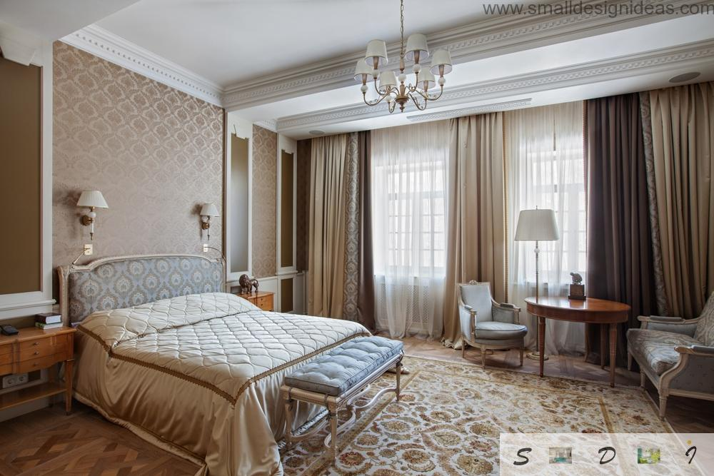 The main bedroom full of light and space, and classic elements along with king size bed and bedside tablewith armchair
