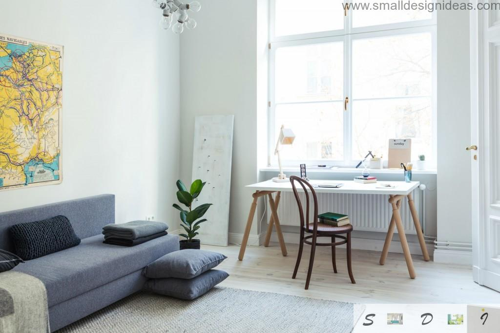 White interior and green plants with dark IKEA sofa in the modern interior with large window