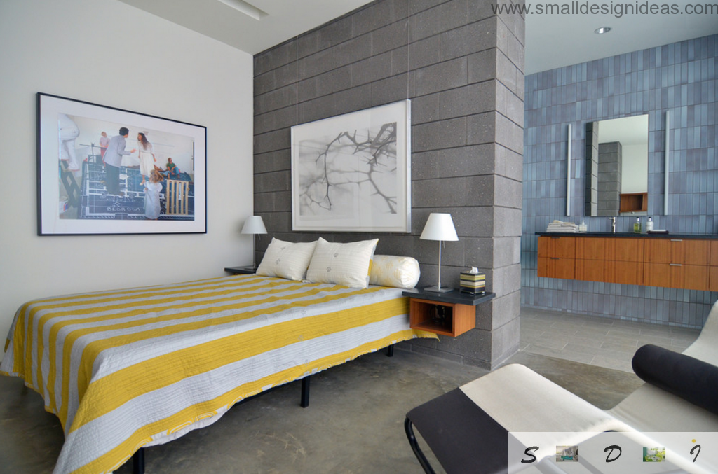 Yellow striped cover on the bed and dark brickwork wall in the hi-tech design of the bedroom
