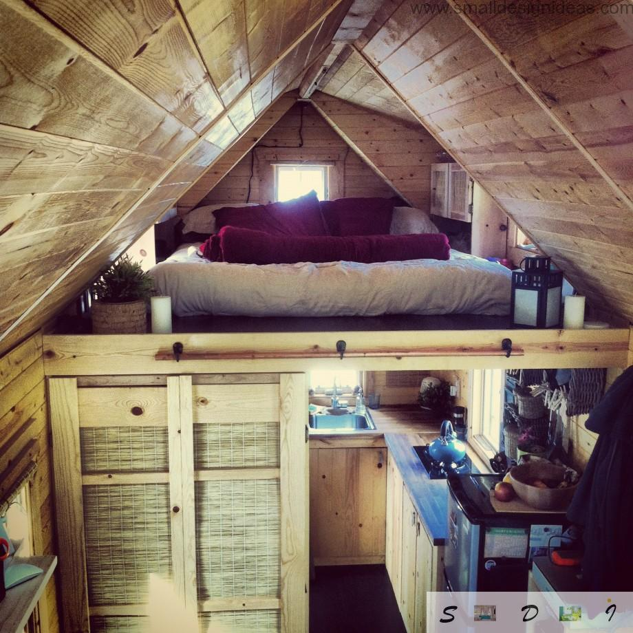 Ladder transforming and cozy bedroom place at the upper tier of the wooden home