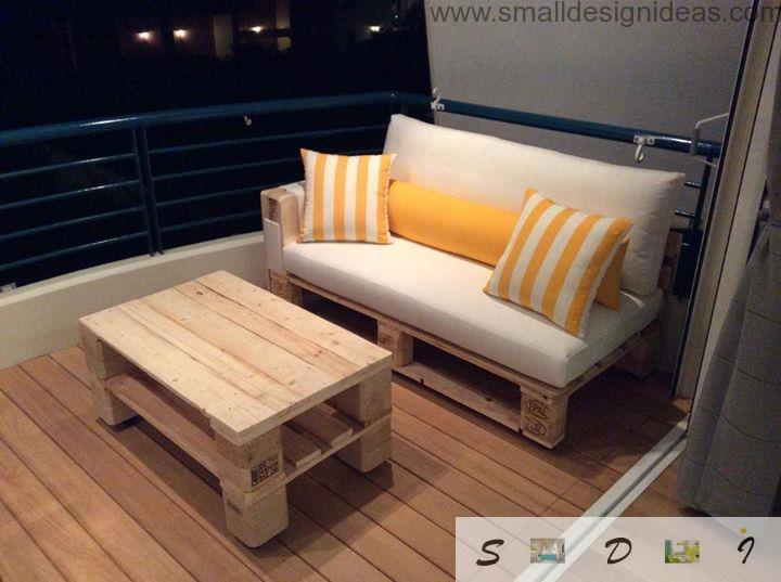 Nice wooden interior with laminate, pallet table and sofa with striped yellow cushions