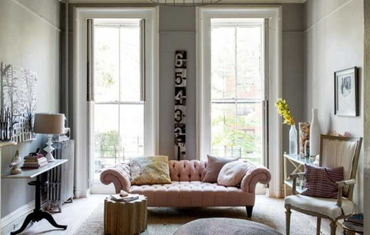 Simple decorated living romo with vintage touch in the form of quilted leather upholstered pink sofa