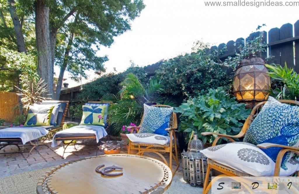 Full of greenery rest zone for guests and owners of the private house with armchairs and sunbeds