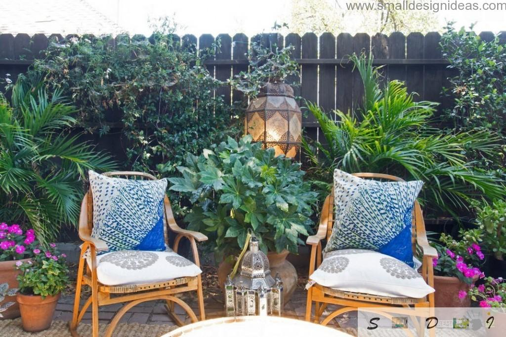 Blue pillows on the rattan armchairs look appropriate and complimenting the overall landscape of the garden