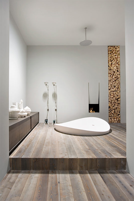 Spa styled bathroom with wooden floor and even firewood rack inside