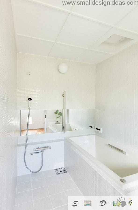 Snow-white tiled bathroom with shower and tub