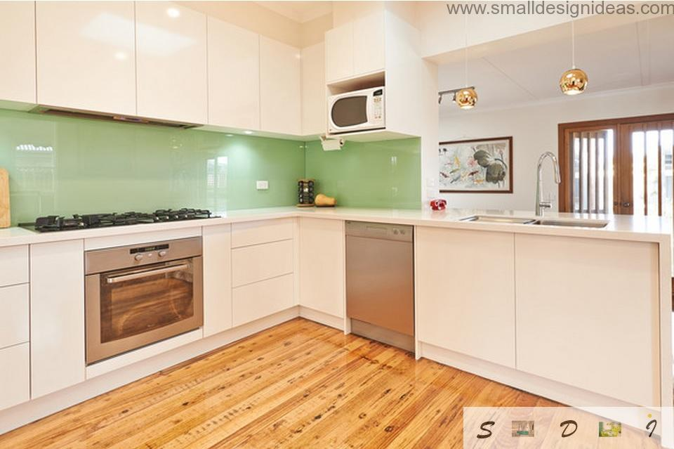 Nice wooden laminate at the floor of bright middle-sized kitchen with light green splashback