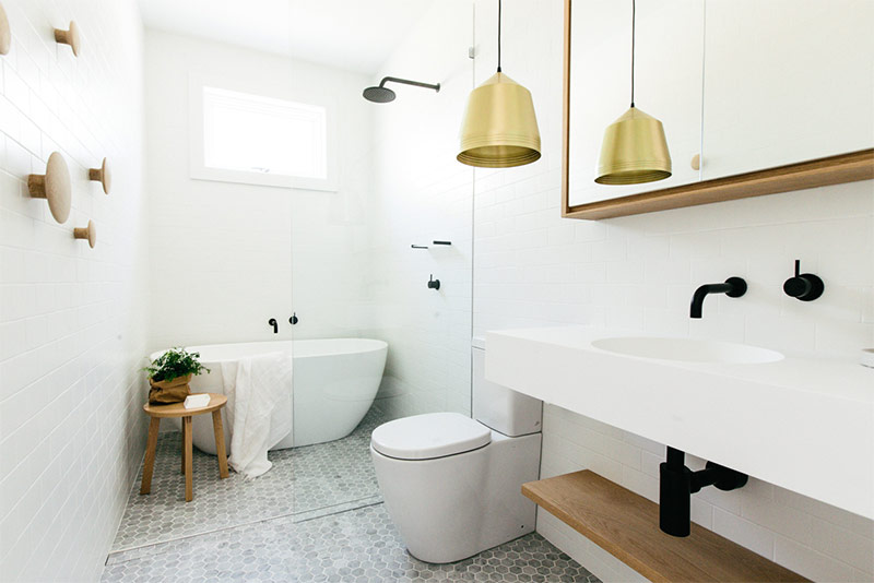 Large traditionally white Scandi bathroom with black exposed plumbing and golden colored lamp