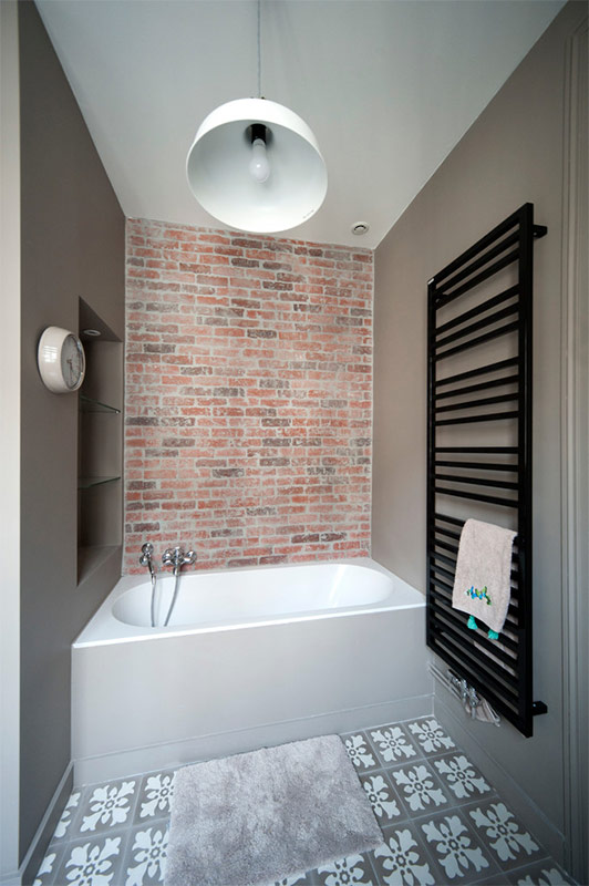 Dark gray walls and accent brickwork along with black towel heater constitute successfully designed interior