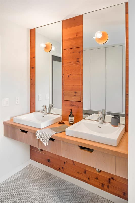 Scandinavian Interior Design Style. Reddish noble wood trimming in the bathroom for two with hovering vanity