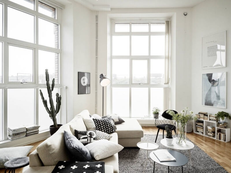 White colored living room space with high ceiling and plenty of natural light through sash windows