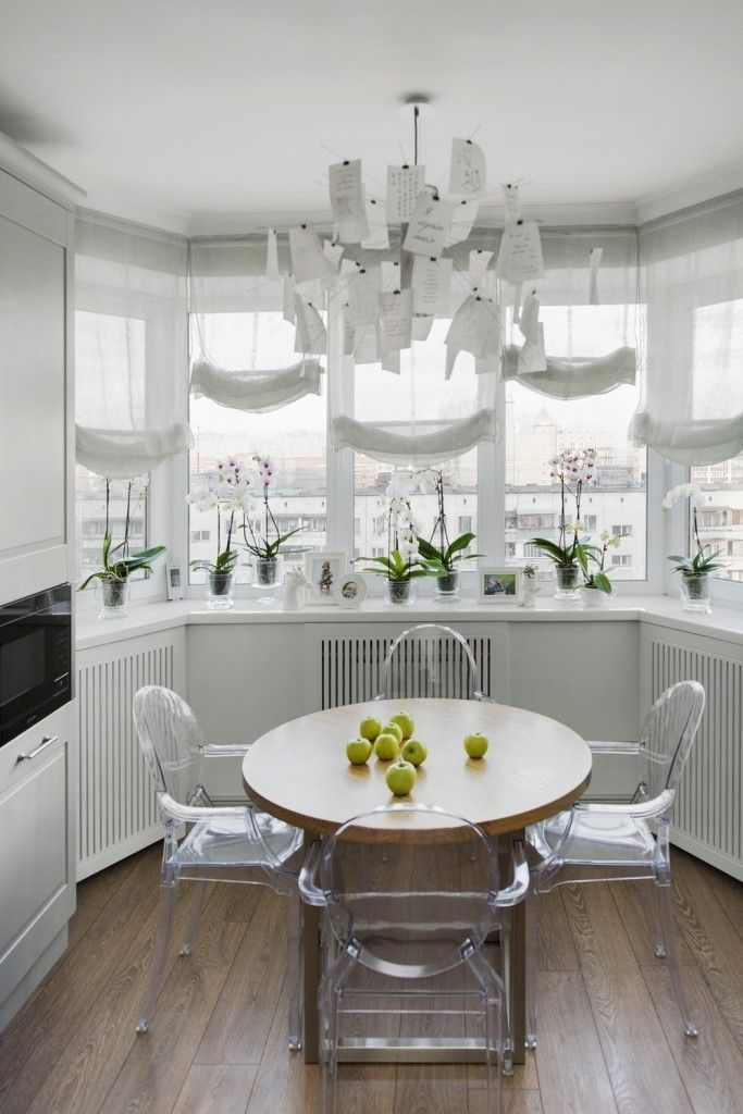 White modern kitchen interior with natural notes and transparent fashionable chairs