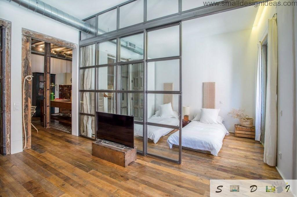 Nice bedroom cell from the steel and glass frame in the Spanish studio apartment