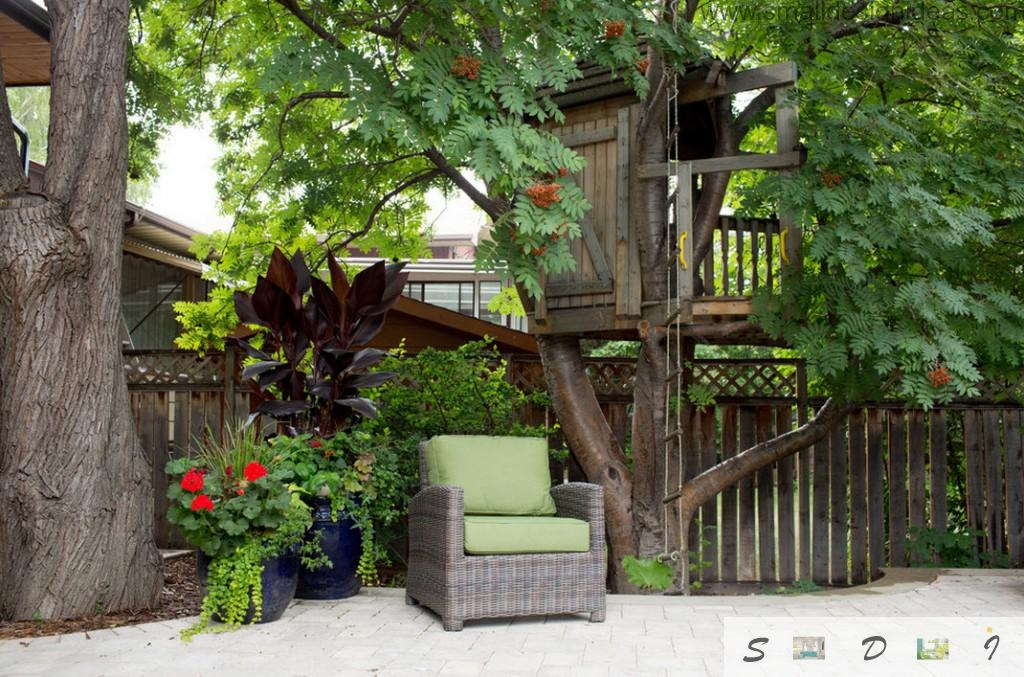 Green chair among the greenery of the private estate and with the small tree house