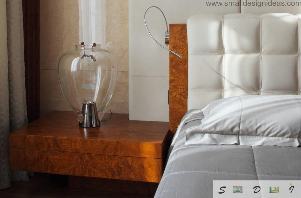 Soft headboard of the bed and the wooden bedside table with nightlamp in close-up
