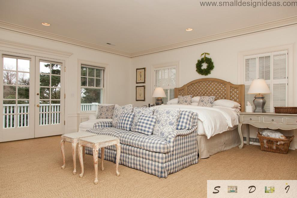 Chess-spottedblue and white sofa in front of the bed in the Provence style