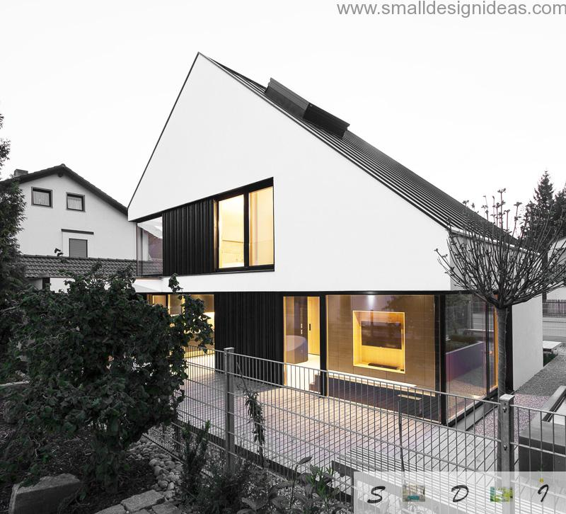 Big two-storey house in black and white contrast with acutely slnated roof and abrupt lines