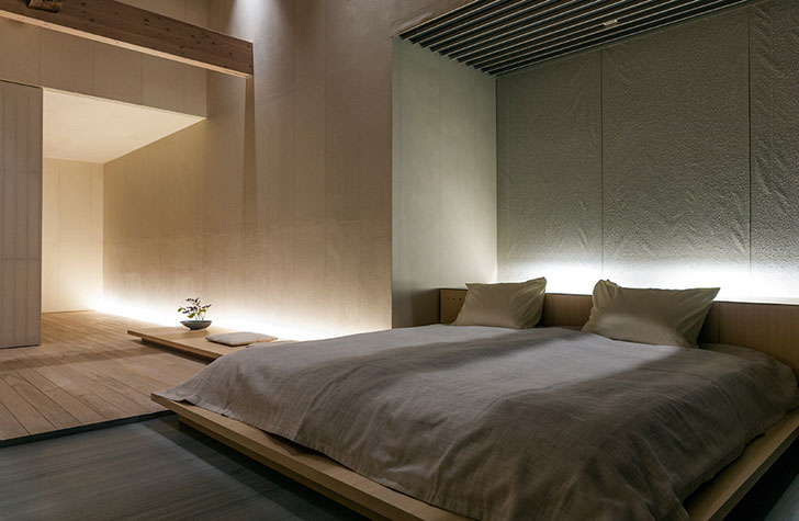 Minimalistic setting of the intimate Japanese bedroom in pastel colors with uintimate backlight and smooth finishing