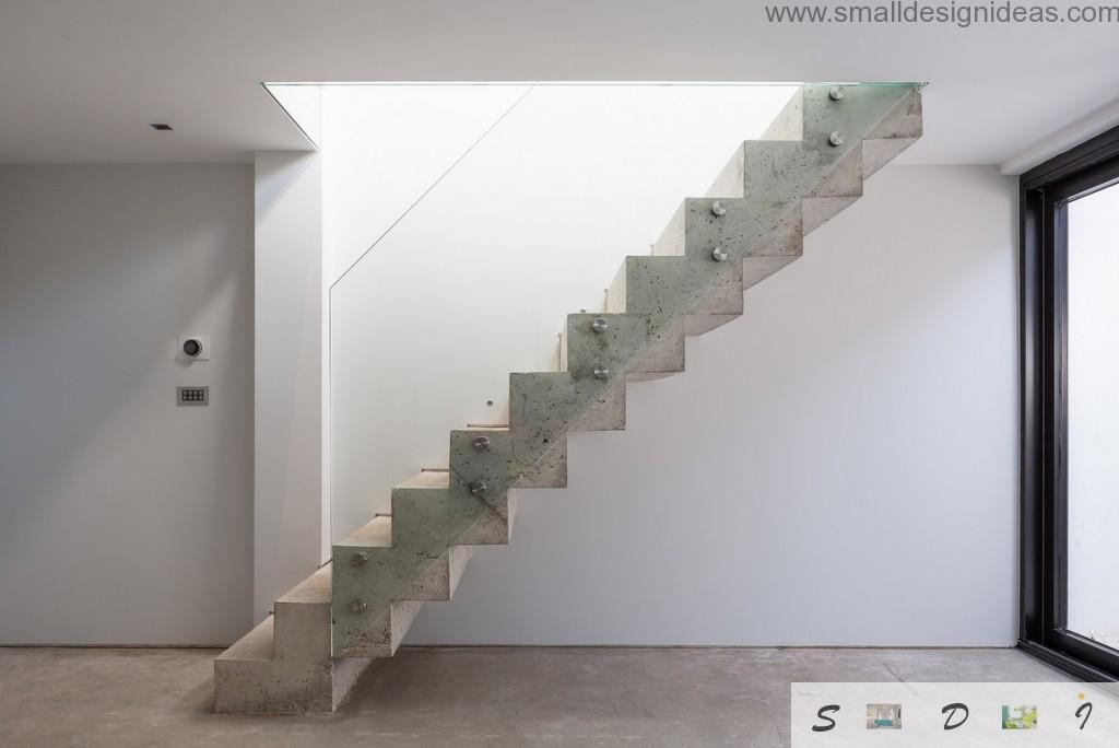 Concrete staircase and glass safe panels as a fashionable element of the modern house interior design