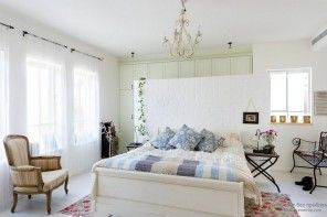 Relaxing and calming atmosphere of the white provencal bedroom with decorative greenery