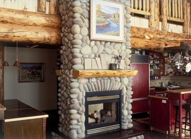 Stone finished fireplace with wooden crowned mantelshelf for rustic living room