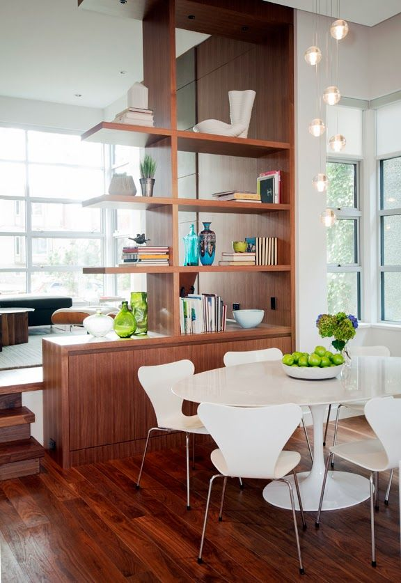 Dining zone railed off with wooden rack with books