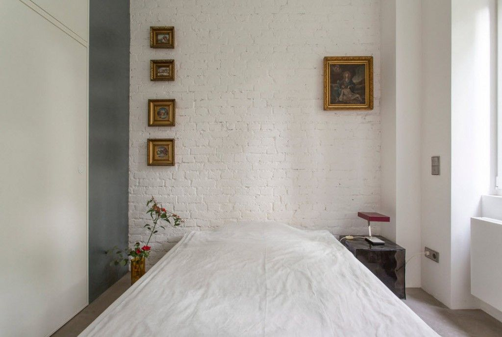 Small 150 Square Feet German Apartment Interior Design Ideas. Austere white bedroom with brickwork