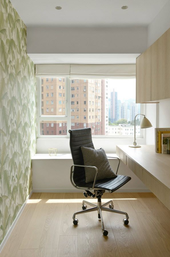 Home office with wallpaper and black armchair