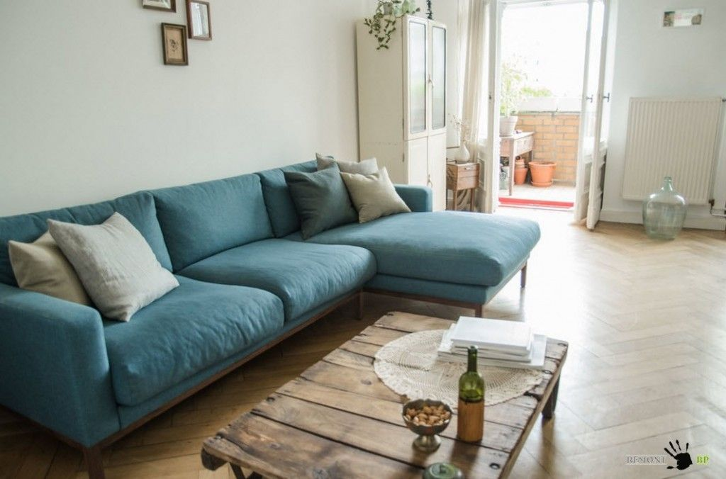 Berlin Apartment Retro Style Modern Interior Design. Blue angle couch and wooden table in the living