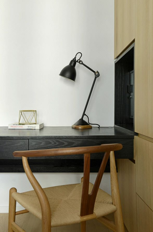 Black wark table and black lamp against the white walls of the home office