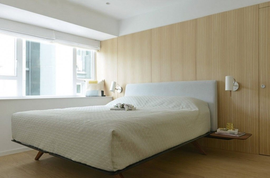 Large wooden screen behind the bed in the bedroom of modern minimalistic Chinese apartment