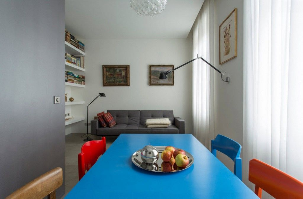 Small 150 Square Feet German Apartment Interior Design Ideas. Dining zone with blue table and colorful chairs