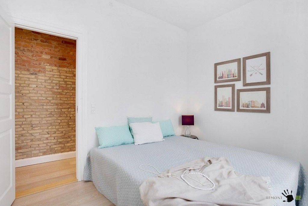 Modest white Scandinavian bedroom decorated with pictures on the wall