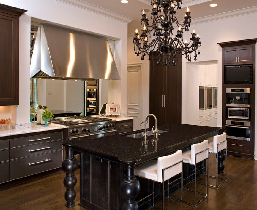 Stylish Kitchen Chandelier Types: Classic to Avant-Garde. Wooden black furniture and steel kitchen set surfaces in the union